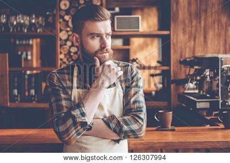 Thoughtful barista. Young bearded man in apron looking away and keeping hand on chin while standing at bar counter.