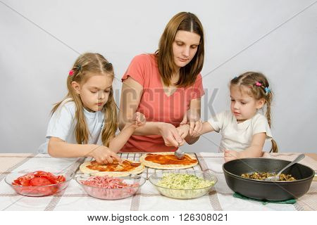 Mom Helps Younger Daughter Spread Ketchup On A Pizza, The Eldest Daughter, She Is Preparing A Second