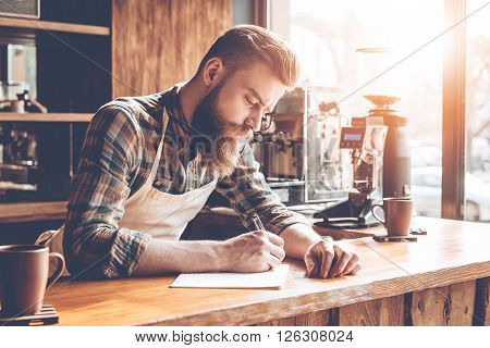 Writing down new coffee recipes. Young bearded man in apron writing in notebook while leaning to bar counter at cafe
