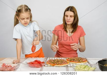 Six Year Old Girl Takes A Plate Of Cutting Tomatoes For Pizza Under The Supervision Of Mum