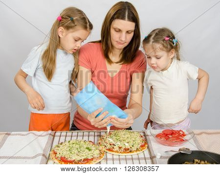 Two Little Girls Are Watching With Interest As The Mother Is Watering Mayonnaise Pizza