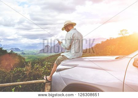 Young man is looking way on navigation via cell telephone during his amazing summer adventure in Thailand. Bearded male is watching photos on smart phone while is sitting on a suv hood against jungle