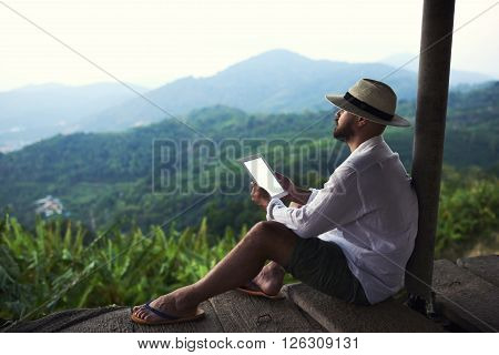 Dreaming man is holding touch pad with copy space on screen while is enjoying amazing jungle view. Male author is admiring beautiful Asian scenery while inspire to write his book via digital tablet