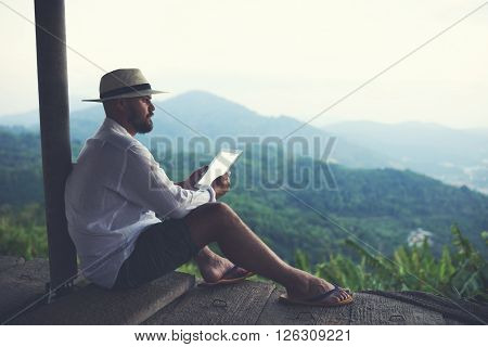 Man wanderer enjoying amazing jungle landscape and holding in hands portable touch pad with copy space on the screen. Young male explorer is using digital tablet while admiring wild mountains nature
