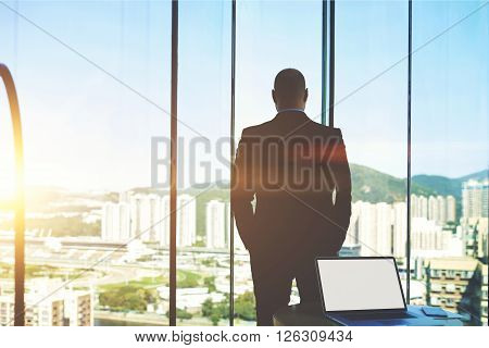 Back view of man in suit is watching in window on a buildings what built his construction company and behind him lying open portable laptop computer with empty blank copy space screen for your content