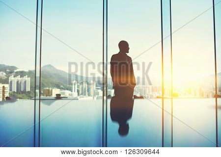 Silhouette of young asian manager is standing in conference room against big window with view of business district. Male is thinking about future his company after unsuccessful meeting with investors