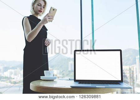 Young female successful lawyer is reading text message on cell telephone while is standing in modern office interior near table with cup of coffee and open net-book with mock up copy space screen