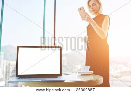 Gorgeous woman prosperous CEO is reading e-mail on cell telephone while is standing in her office near table with open laptop computer with mock up copy space screen for your advertising text message