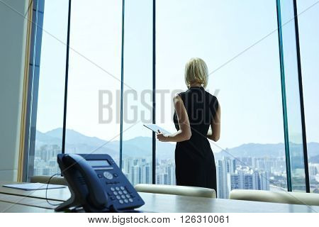 Woman proud CEO with digital tablet in hands thoughtful is looking into the office window while is standing in skyscraper interior in big conference room with table. Copy space for advertising text