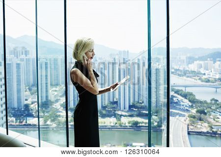 Young woman successful manager of big thriving company having cell telephone conversationwhile is standing with touch pad in hand against cityscape view outside office window.Copy space for content