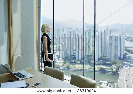 Confident woman business owner with digital tablet in hand is thinking about future meeting with investors while is watching on developed Hong Kong city view with tall skyscrapers outside the window