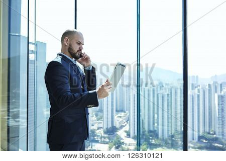 Serious businessman in luxury suit with digital tablet in hand dissatisfied with fall of quotations his shares on international stock exchanges is talking via mobile phone with his finance director