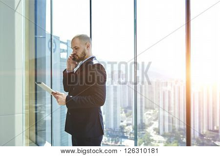 Man owner of prosperous real estate company with touch pad in hand is calling to his client to find out whether he accepted the decision to buy while is standing in office near window with copy space