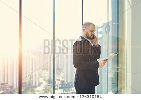 Young bearded man entrepreneur is phoning via mobile phone and studying the norms and documents of an international organizations via digital tablet.Businessman is standing near window with copy space