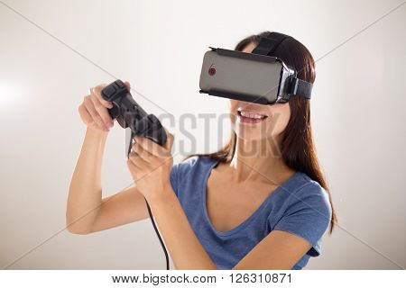 Asian Woman play video game though VR device
