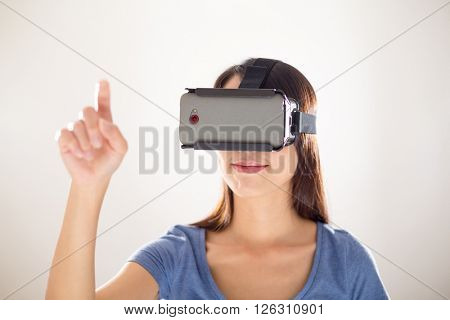Asian Woman wearing with virtual reality device and finger point up