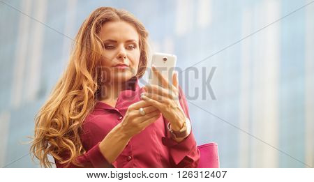 Businesswoman looking at her mobile phone and typing something. Long-haired woman in vivaceous blouse posing in the city centre.