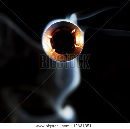 Hollow pointed bullet with smoke behind on a black background