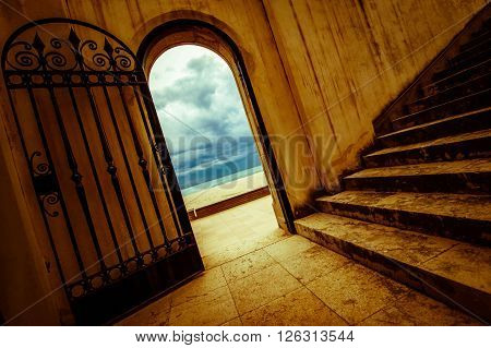 mysterious, vintage old gate and stairs to spanish dramatic beach