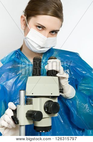 young girl looking through a microscope
