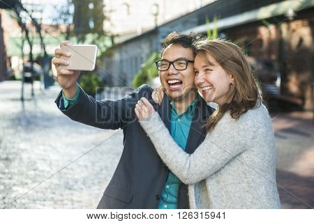 Two laughing young people taking a selfie with mobile device outside on city street