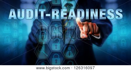 White collar worker touching AUDIT-READINESS on an interactive screen. Business metaphor and information technology concept for continuous documentation and compliance in preparation for auditing.