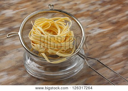 Raw noodle pasta in metal kitchen sieve over painted textile background