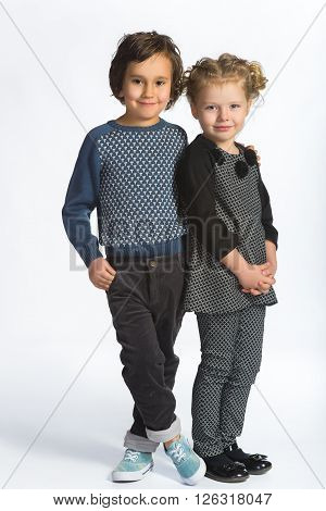 Cute boy and girl or teenagers in full length casual style blue jeans posing.