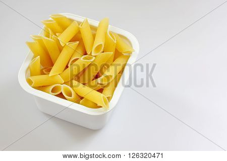 Raw penne rigate pasta in the plastic box over light background