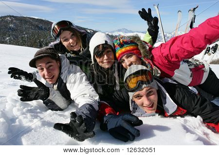 Group of teenagers laid in the snow