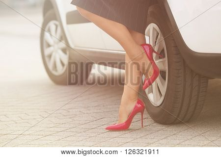 Businesswoman posing near white car and showing her slim and slender legs near her car. Successful lady in grey skirt posing on pink high heels. Toned image.