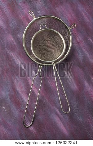 Pair of empty kitchen sieves over painted textile background. Overhead view.