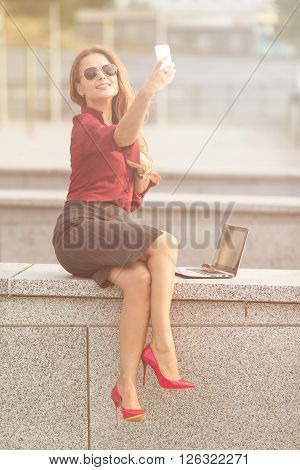 Businesswoman making selfies outdoors and sending photos to her friends and collegues. Smiling lady in sunglasses working in the street. Toned image.