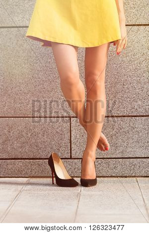 Picture of beautiful woman's legs in full length isolated on brick wall. Lady in yellow dress put off right leg and hid it behind left one. Toned image.
