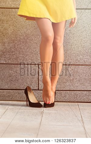 Picture of exhausted woman's legs in full length after hard working day. Girl posing near brick wall. She put off one of her heels. Toned image.