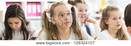 Close-up of a schoolgirl with interested look on her face sitting next to other schoolgirls