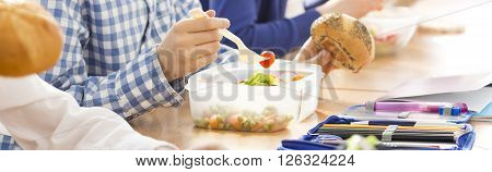 Close-up of a lunch box full of vegetables on a schoolboy's desk