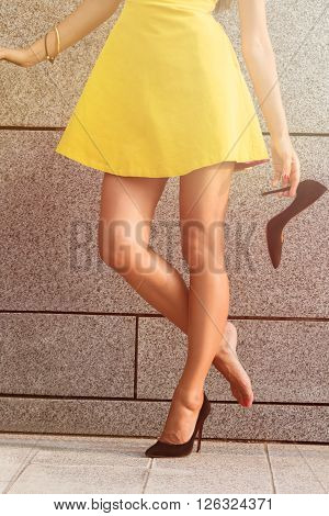 Beautiful woman in yellow dress holding one heel in her hand. Woman's legs in full length. Girl put off one heel to have a rest. Toned image.