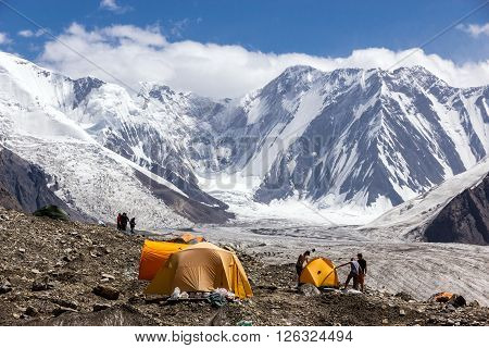 Group of Alpine Climbers Working on setting up Camping Tents at Side Rocky Moraine of Glacier and High Altitude Mountain Range on Background
