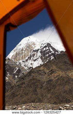 High Mountain Peak and Rock Ridge throw Window Entrance Door of Base Camp Tent Blue Sky and Cloud