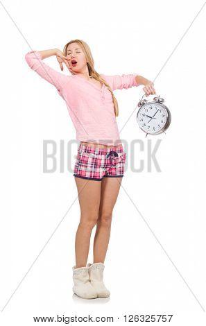 Pretty yawning girl holding alarm-clock isolated on white