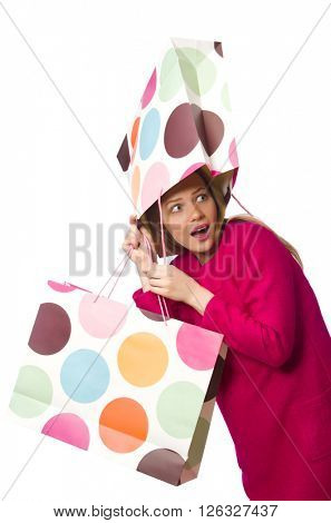 Shopper girl in pink dress holding plastic bags isolated on whit