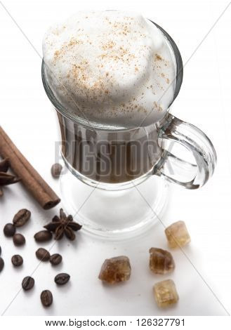 Cappuccino or latte popular hot drink of the day. With thick milk foam and cinnamon. Decorated coffee beans spices and caramel. Frappe clear glass on the white background top view.