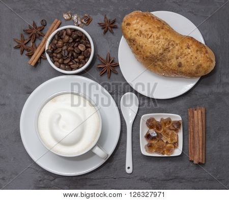 Coffe a cup of hot latte or cappuccino with bun top view. Background plate made from natural slate. Coffe beans sugar cinnamon and decorative star anise for love drink. Coffee shop.