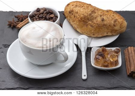 Cup of coffee cappuccino with milk foam on a saucer fresh baked bun caramelized sugar coffee beans cinnamon. Popular morning Breakfast. on a black background plates of slate.
