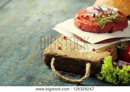 Raw Ground beef meat Burger steak cutlets with seasoning on vintage wooden boards