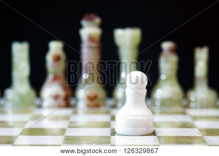 White pawn made from Onyx against other chess pieces on board