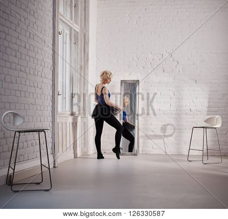 Ballet dancer practicing in studio front of mirror.