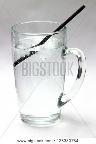 Drinking water. Daily drink a glass of very cold water life giving water. Crystal clear water with ice in a transparent glass on a white background.