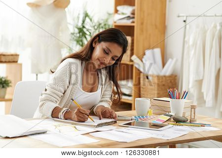 Female fashion designer enjoying working in studio